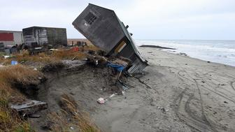 Shishmaref, UNITED STATES:  TO GO WITH AFP STORIES A home destroyed by beach erosion tips over 27 September 2006 in the the Alaskan village of Shishmaref. The village, home of Inupiat Eskimos, is located some 600 miles (965kms) northwest of Anchorage but just 110 miles (177kms) from the east coast of Russia. Shishmaref, on an island reachable only by air and inhabited for 4,000 years, is facing evacuation because of global warming. Temperatures that have risen 15F (4.4C) over the last 30 years are causing a reduction in sea ice, thawing of permafrost along the coast, making the shoreline vulnerable to erosion. The census of 2000 reported there were 562 people, 142 households, and 110 families residing in the village all facing evacuation and the loss of their traditional life. AFP PHOTO/GABRIEL BOUYS    =MORE PHOTOS IN IMAGE FORUM=  (Photo credit should read GABRIEL BOUYS/AFP/Getty Images)