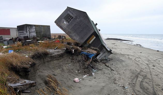 A home destroyed by beach erosion tips over in September 2006 in the Alaskan village of