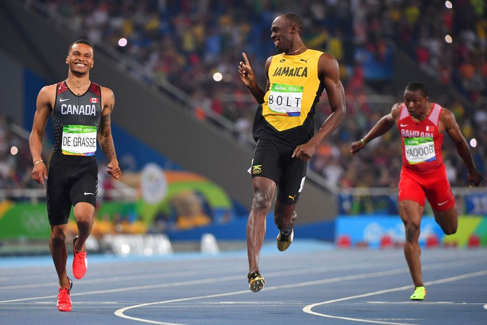 Jamaica's Usain Bolt jokes with Canada's Andre De Grasse after they crossed the finish line in the Men's...