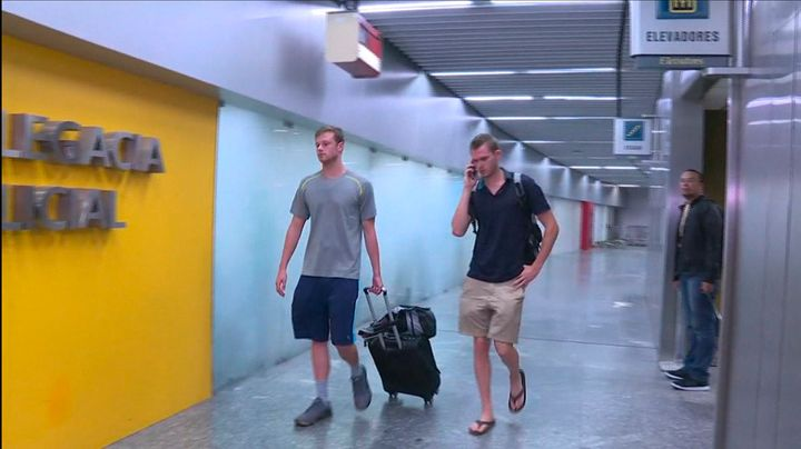 U.S. swimmers Jack Conger (L) and Gunnar Bentz walk into a police office of Rio de Janeiro's international airport after they