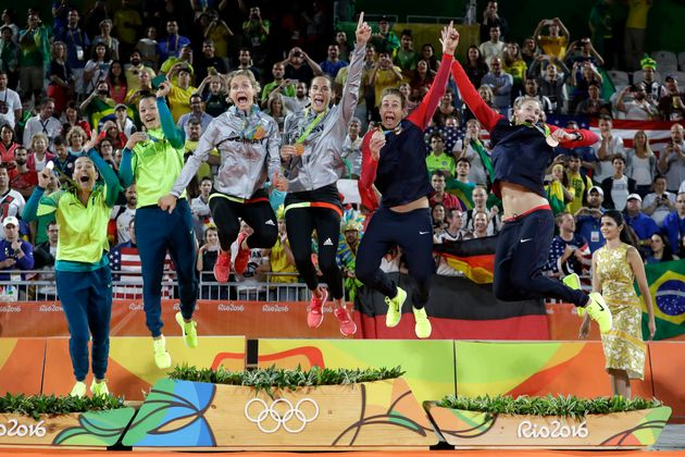 Medalists jump off the podium after the medals ceremony in the women's beach volleyball