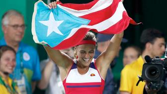 Monica Puig of Puerto Rico celebrates holding her country's flag after winning the gold medal match in the women's tennis competition at the 2016 Summer Olympics in Rio de Janeiro, Brazil, Saturday, Aug. 13, 2016. (AP Photo/Vadim Ghirda)