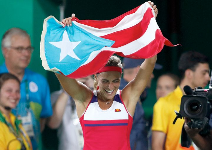Monica Puig of Puerto Rico celebrates holding her country's flag after winning the gold medal match in the women's tennis com