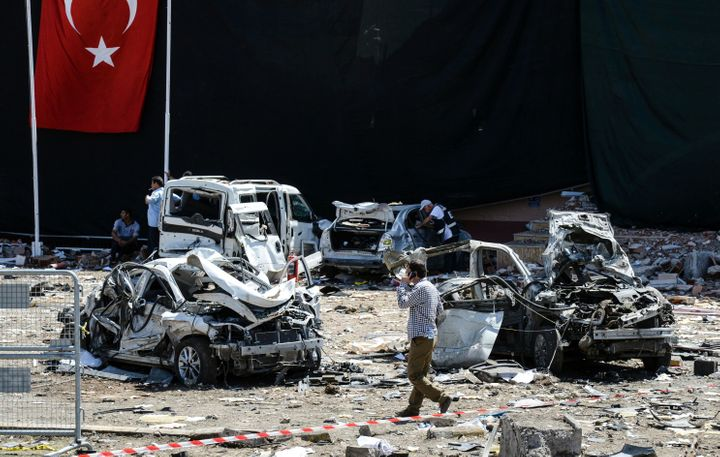 A man walks among the wreckage of vehicles as Turkish rescue workers and police inspect the blast scene following a car bomb