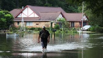 BATON ROUGE, LA - AUGUST 15:  Ryan Evans walks along a flooded road on August 15, 2016 in Baton Rouge, Louisiana. Record-breaking rains pelted Louisiana over the weekend leaving the city with historic levels of flooding that have caused at least seven deaths and damaged thousands of homes.  (Photo by Joe Raedle/Getty Images)