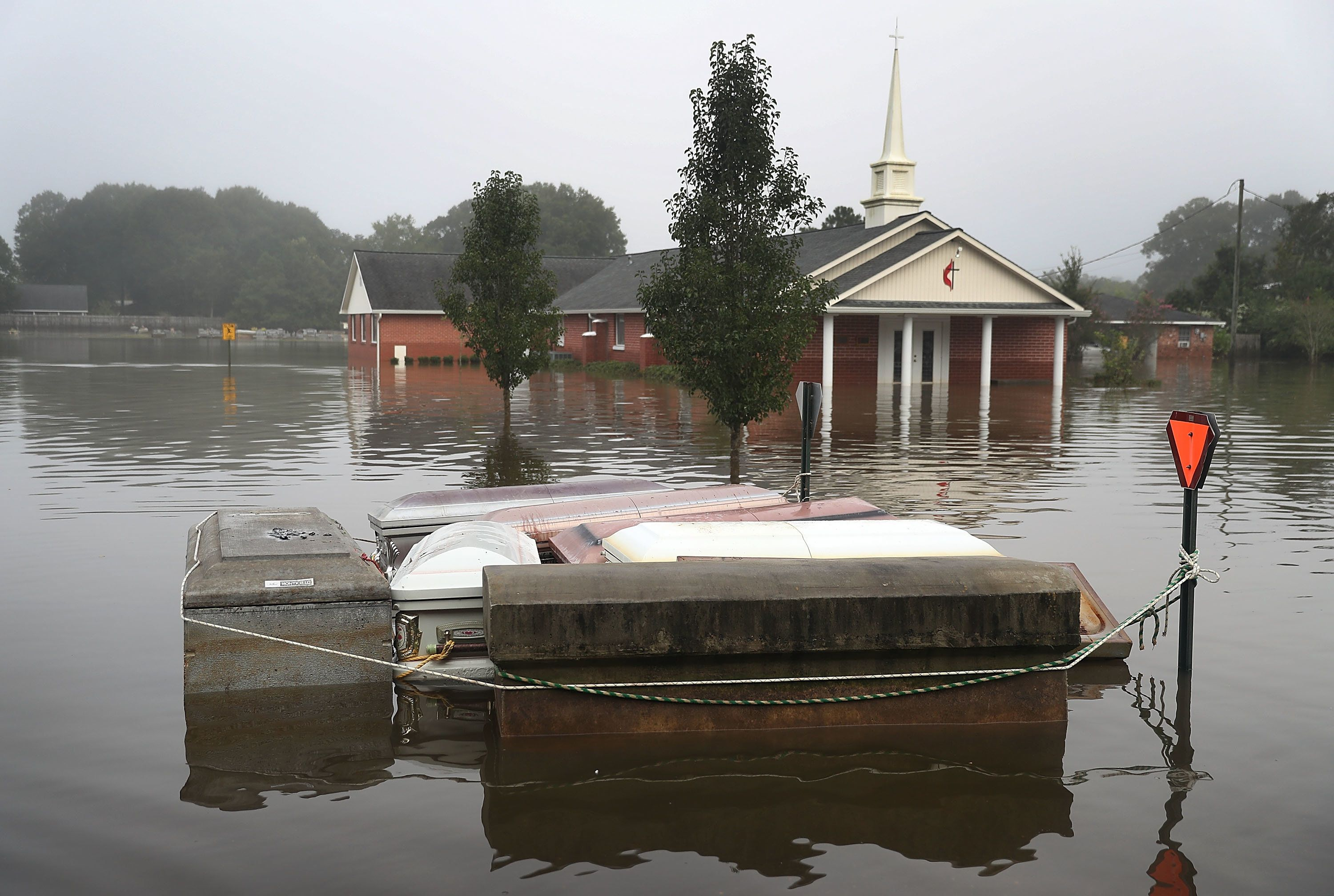 Caskets are seen floating in flood waters near a cemetery on Aug. 17 in Gonzales, Louisiana.