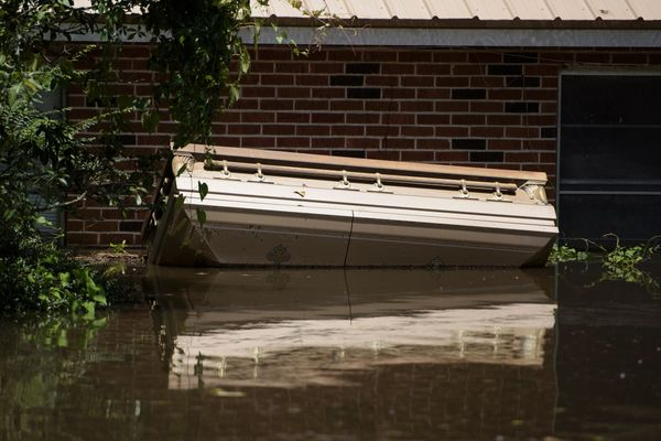 A casket floats up against a house in Gonzales, Louisiana, on Aug. 16.