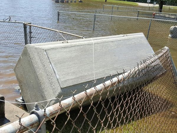 A concrete casket cover is tipped over by flood water in Springfield on Aug. 15.
