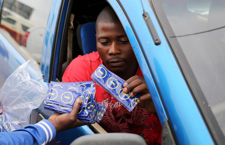 A taxi driver is given condoms by a member of the Treatment Action Campaign (TAC) as they campaign for safe sex in Daveyton,