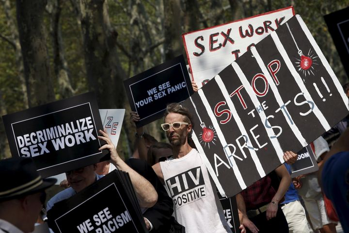 Demonstrators hold signs as they protest the arrests of male escort service Rentboy.com staffers in 2015.