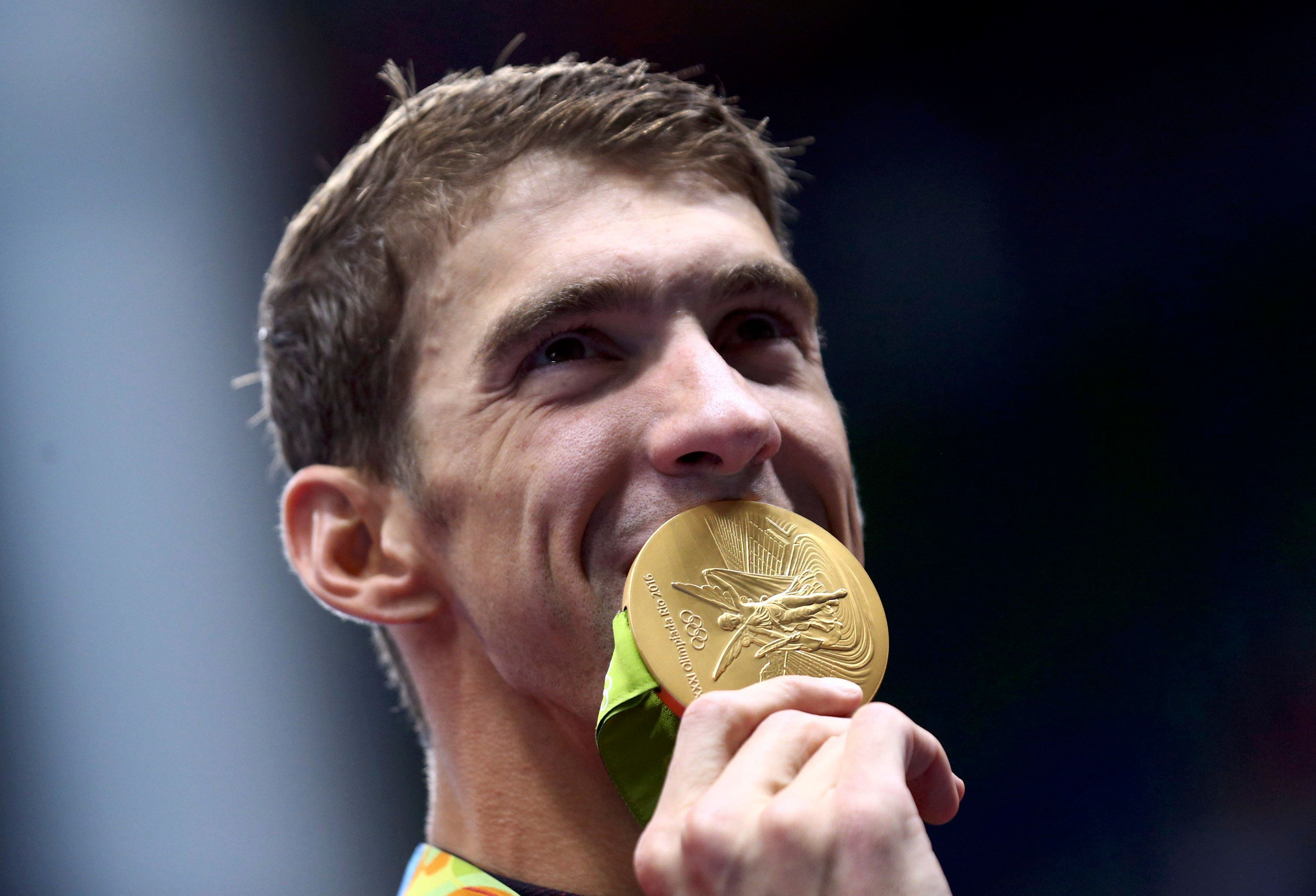 2016 Rio Olympics - Swimming - Victory Ceremony - Men's 4 x 100m Medley Relay Victory Ceremony - Olympic Aquatics Stadium - Rio de Janeiro, Brazil - 13/08/2016. Michael Phelps (USA) of USA poses with his gold medal.  REUTERS/Marcos Brindicci TPX IMAGES OF THE DAY FOR EDITORIAL USE ONLY. NOT FOR SALE FOR MARKETING OR ADVERTISING CAMPAIGNS.