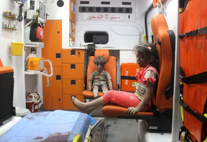 ALEPPO, SYRIA - AUGUST 17: 5-year-old wounded Syrian kid Omran Daqneesh (C) sits with his sister (R) in the back of the ambul