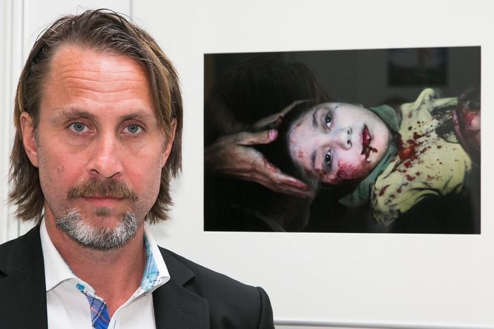 Swedish war photographer Niclas Hammarstraam poses with his photo of Dania, an 11-year-old girl who was hit by shrapnel while