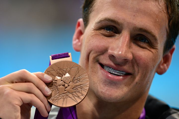 "American swimmer Ryan Lochte poses at the&nbsp;2012 Olympic with his bronze medal and silver <a href=""http://www.nytimes.com/"