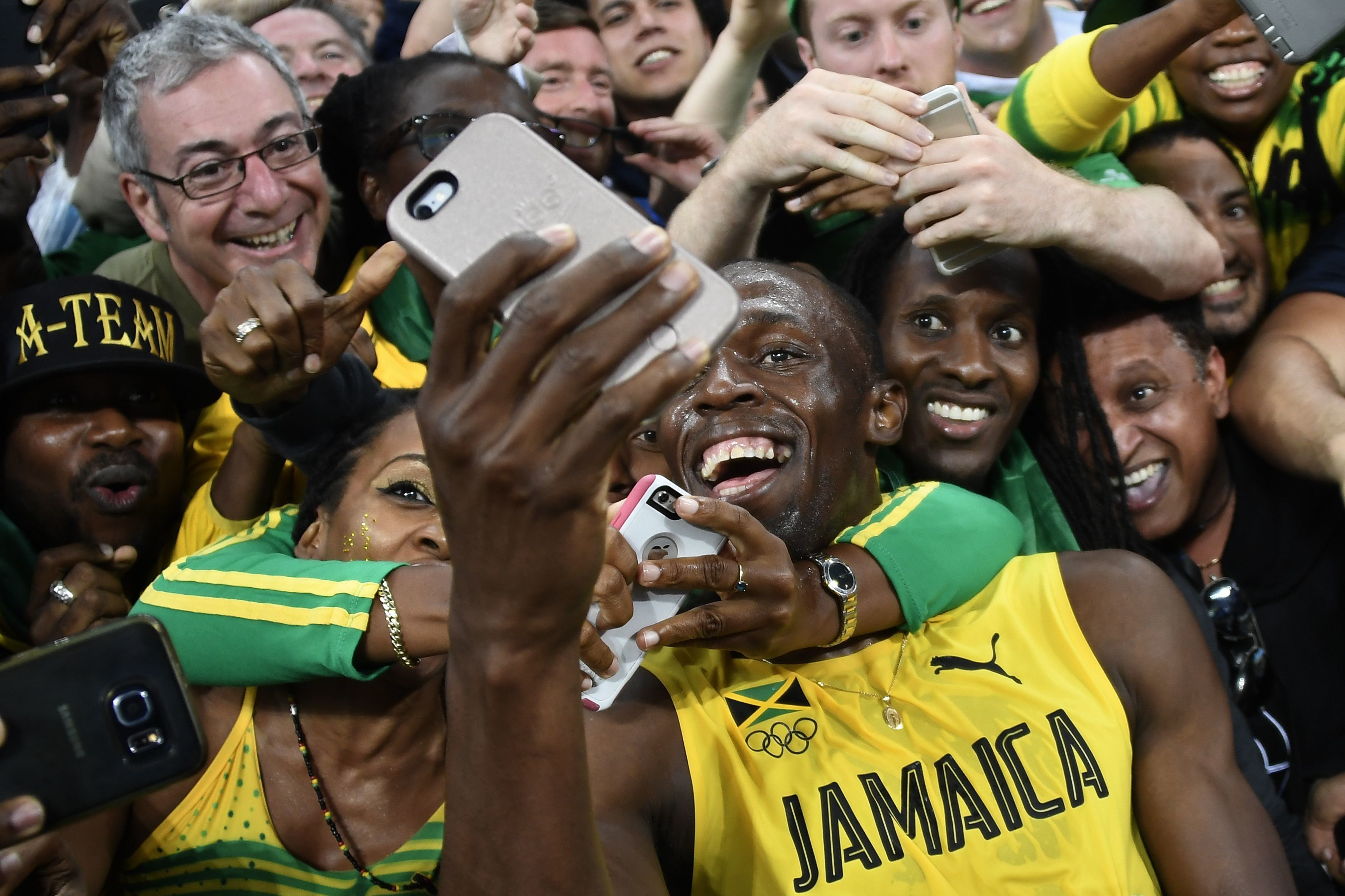 Jamaica's Usain Bolt takes selfie photos as he celebrates with fans after winning the Men's 200m Final during the athletics event at the Rio 2016 Olympic Games at the Olympic Stadium in Rio de Janeiro on August 18, 2016.   / AFP / Damien MEYER        (Photo credit should read DAMIEN MEYER/AFP/Getty Images)