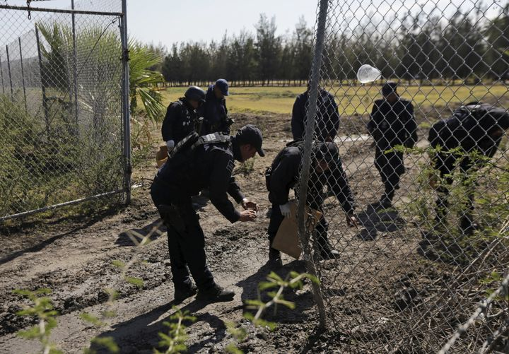 Police officers collect evidence at the ranch. The Jalisco New Generation Cartel hit security forces hard in the weeks before