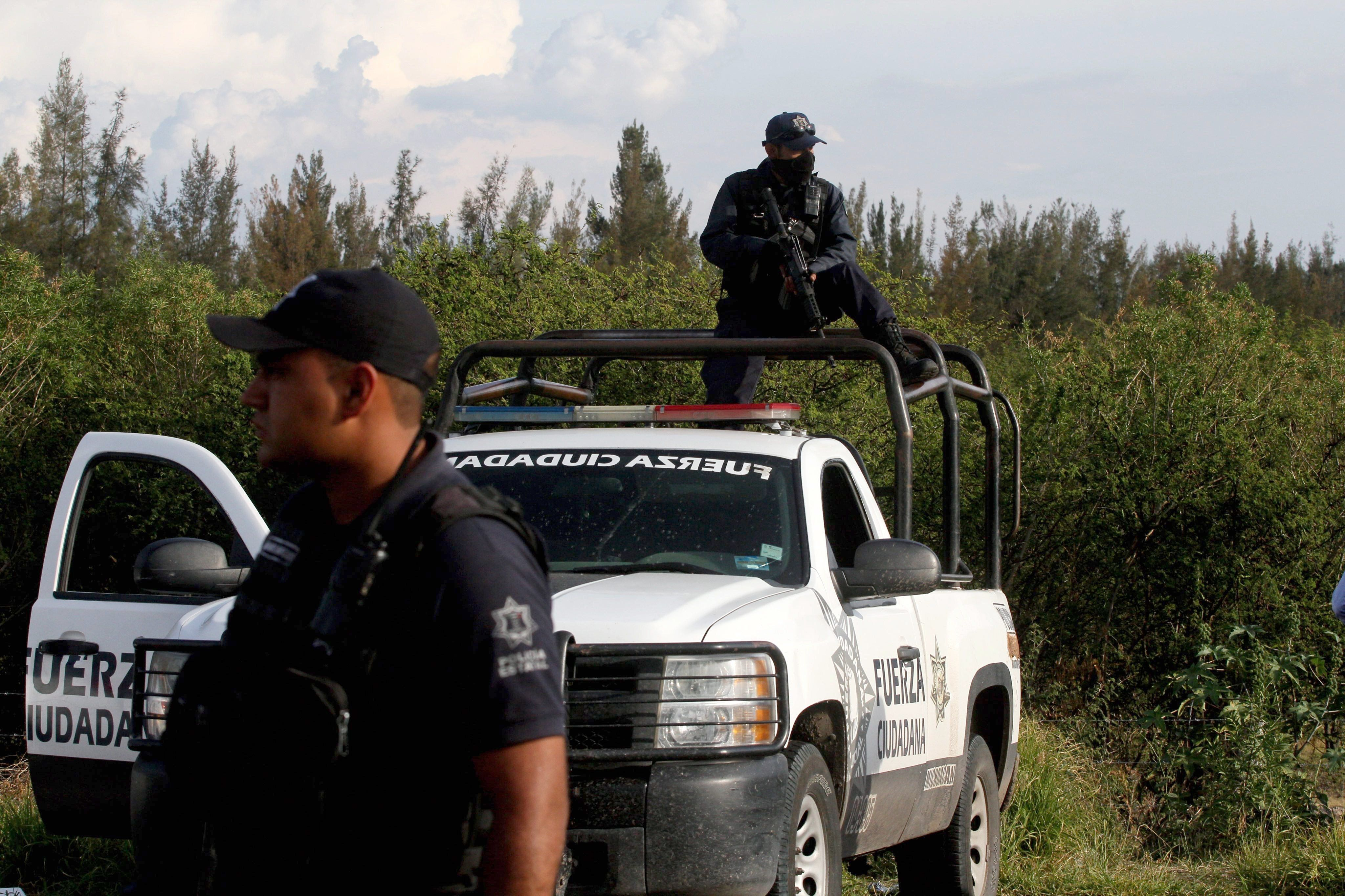Members of the State police stand guard at the entrance of the ranch where gunmen took cover during an intense gun battle with the police, along the Jalisco-Michoacan highway in Vista Hermosa, Michoacan State, on May 22, 2015. At least 37 people were killed in the gunfight in Mexico's troubled western state of Michoacan, in one of the bloodiest clashes in the country's drug war. Two police officers also died in the shootout in the municipality of Tanhuato, near the border with Jalisco state, a federal government official told AFP. Michoacan and Jalisco have endured some of the worst violence in a drug war that began to escalate in 2006, when the government deployed troops to combat cartels. More than 80,000 have been killed and another 22,000 gone missing nationwide in the past nine years.  AFP PHOTO / HECTOR GUERRERO        (Photo credit should read HECTOR GUERRERO/AFP/Getty Images)