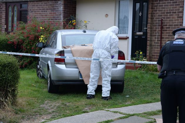 A forensics officer examines evidence at the scene of the
