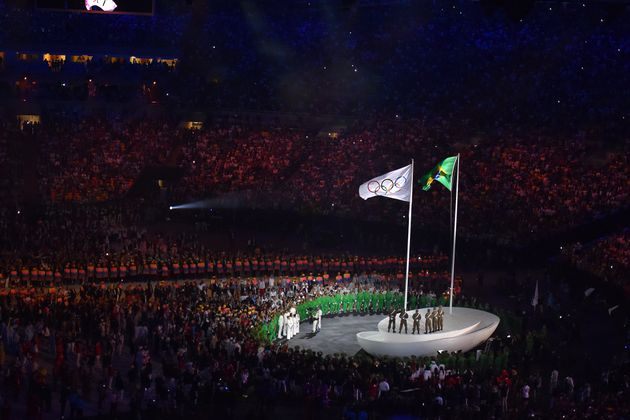 The Brazilian and Olympic flag fly over the opening
