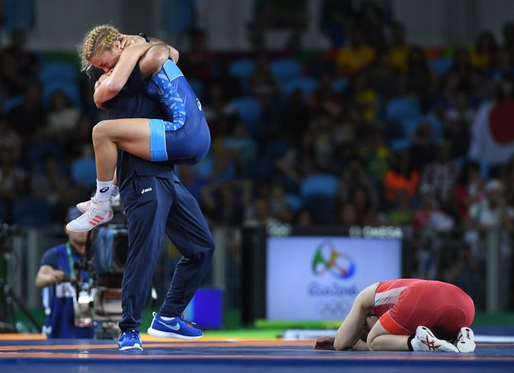 Saori Yoshida buries her face in the mat as U.S. wrestler Helen Maroulis celebrates her gold-medal win in the 53kg wrestling