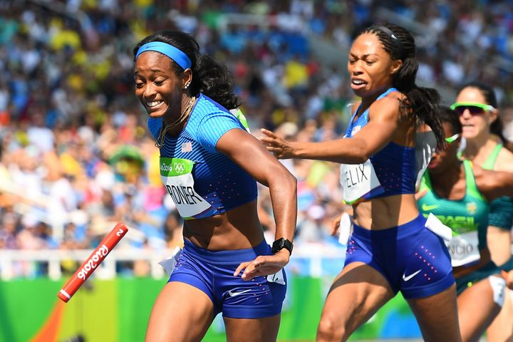 Allyxon Felix attempts to hand the baton to English Gardner in Round 1 of the women's 4x100-meter relay trials on Aug. 1