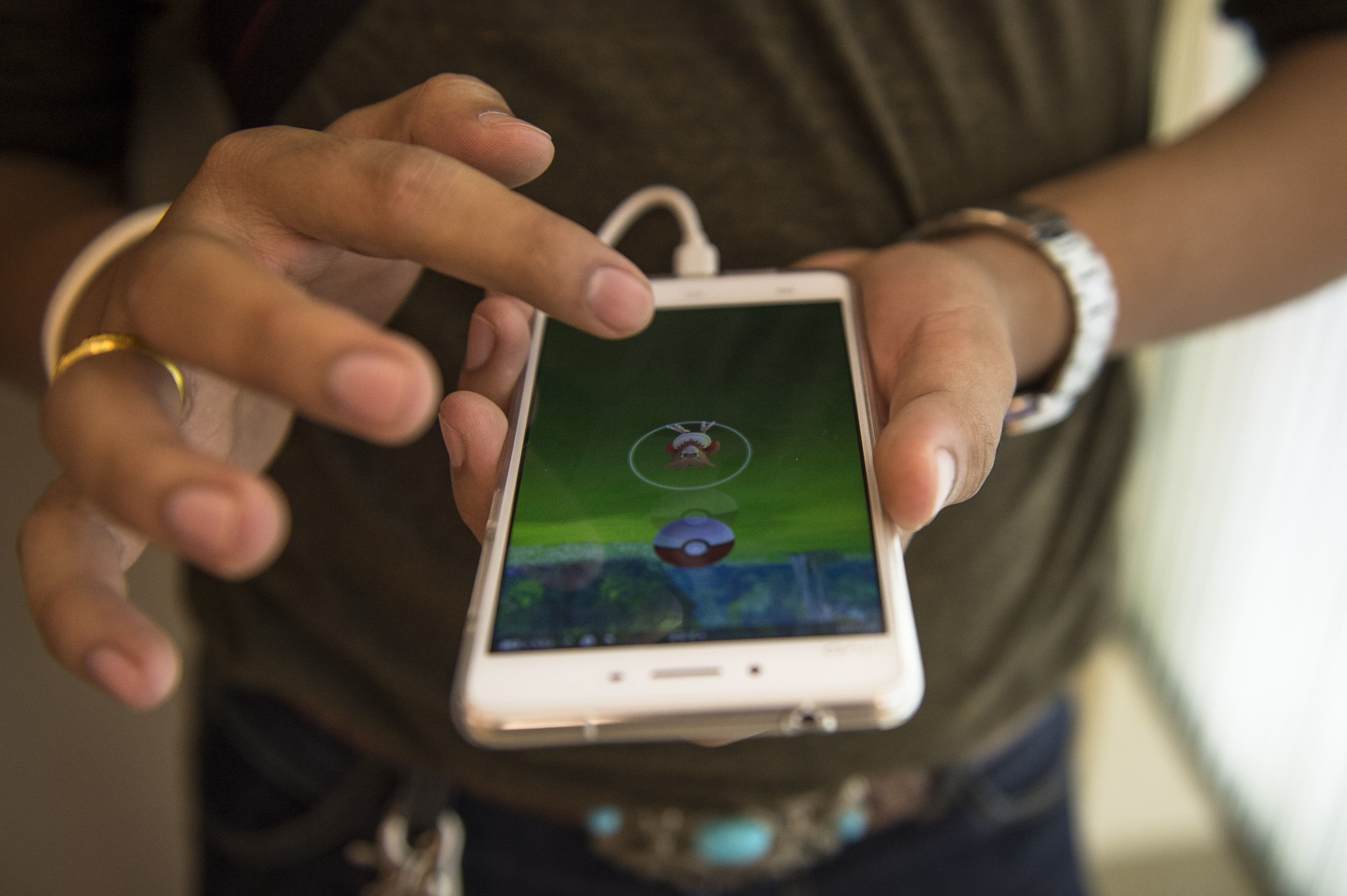 A gamer plays Pokemon Go on his mobile phone in a shopping mall in Bangkok on August 9, 2016. Pokemon Go's debut in Thailand has alarmed the country's generals, prompting the kingdom's junta chief to warn youngsters against playing too much and the army to ban the game from barracks. The mobile app was made available in Thailand on August 6, delighting many in a country where Japanese subcultures have a significant following.   / AFP / LILLIAN SUWANRUMPHA        (Photo credit should read LILLIAN SUWANRUMPHA/AFP/Getty Images)
