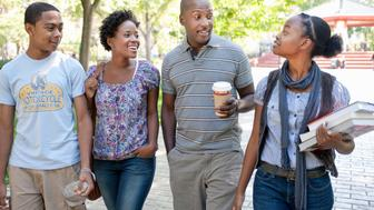 three black teens walking with black adult teacher in urban park