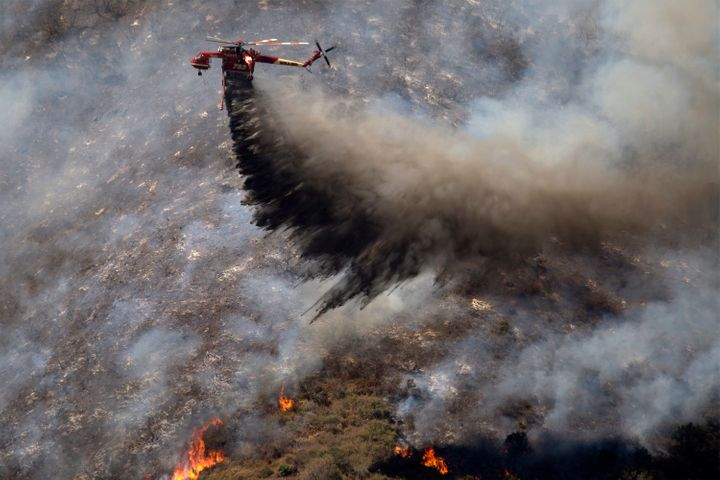 A firefighting helicopter makes a drop as firefighters try to gain control of the fire above homes along Cajon Boulevard at t