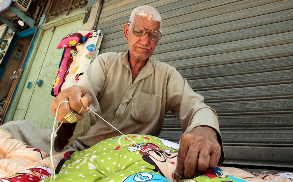 Abu Abdul Razzaq, 74, sews blankets on the streets of Baghdad, Iraq. Razzaq is one of the last people to work in a local indu