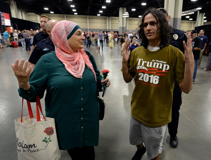 Rose Hamid, left, and Jake Anantha, right, are escorted from the Charlotte Convention Center in Charlotte, N.C., prior to a r