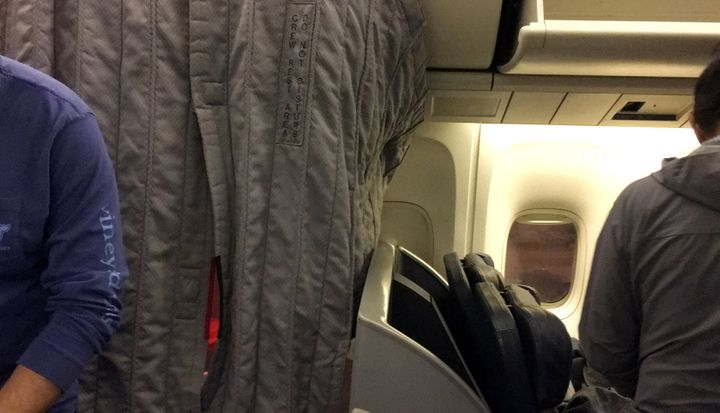 The curtain of the crew section of a passenger plane covers U.S. Swimmers Jack Conger and Gunnar Bentz during their overnight