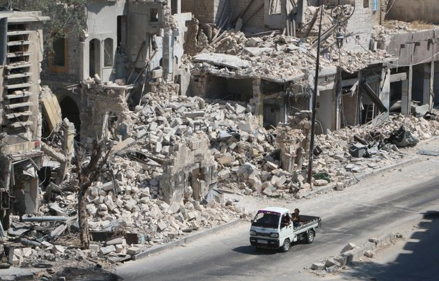 Russian cruise missiles targeted Syria on Friday. Pictured here,men ride on a pick-up truck past...