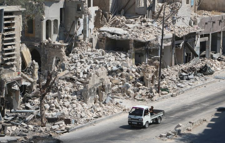 Russian cruise missiles targeted Syria on Friday. Pictured here, men ride on a pick-up truck past damaged buildings in t