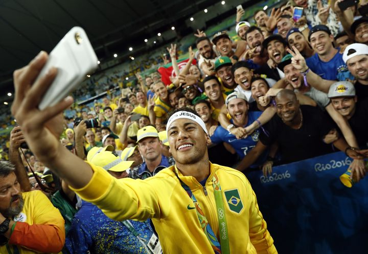 Brazil's forward Neymar poses for a selfie with fans at the Maracana stadium as they celebrate after the gold medal matc