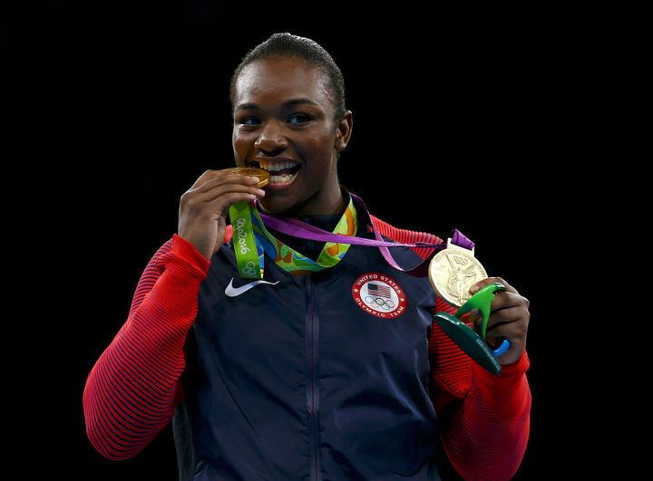 Gold medallist Claressa Shields (USA) bites her medal from Rio 2016 while posing with her other medal from London 2012.