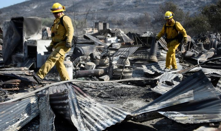 Firefighters walk over the remains of a barn destroyed by the so-called Blue Cut Fire in the San Bernardino National Forest i