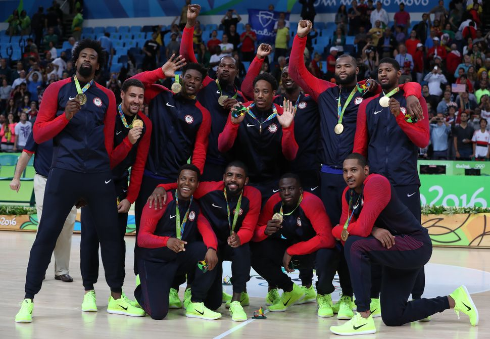 The United States Men's Basketball team celebrate with their gold medals while some mark the moment with their fists raised.