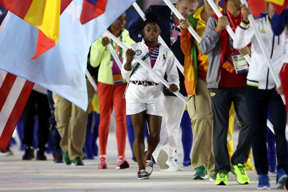 RIO DE JANEIRO, BRAZIL - AUGUST 21:  Flag bearer Simone Biles of United States walks during the 'Heroes of the Games' segment