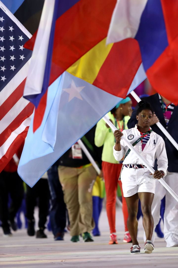 U.S. gymnastic phenom Simone Biles carries the American flag at the Rio Closing Ceremony.