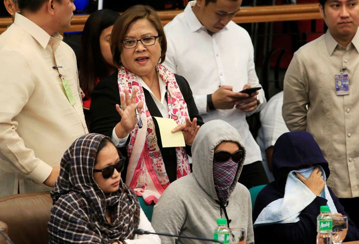 Senator Leila De Lima, chairperson of the Committee on Justice and Human Rights, gestures as she stands near relatives of sla
