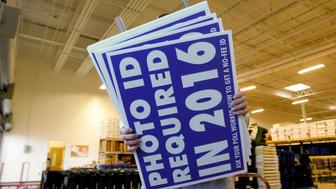 A worker carries a sign that will be displayed at a polling place that will inform voters of the new voter ID law that goes into effect in 2016 at the Mecklenburg County Board of Elections warehouse in Charlotte, North Carolina November 3, 2014. REUTERS/Chris Keane (UNITED STATES - Tags: POLITICS)