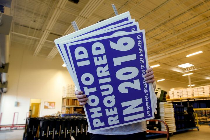 A worker carries a signinformingvoters of avoter ID law intended to go into effect in 2016 in Charlotte, No