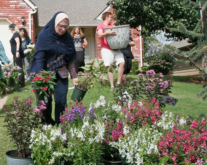Sandra Rana, left, carries flowers to a memorial display on the lawn of the Jabara family in Tulsa, Aug. 19, 2016.