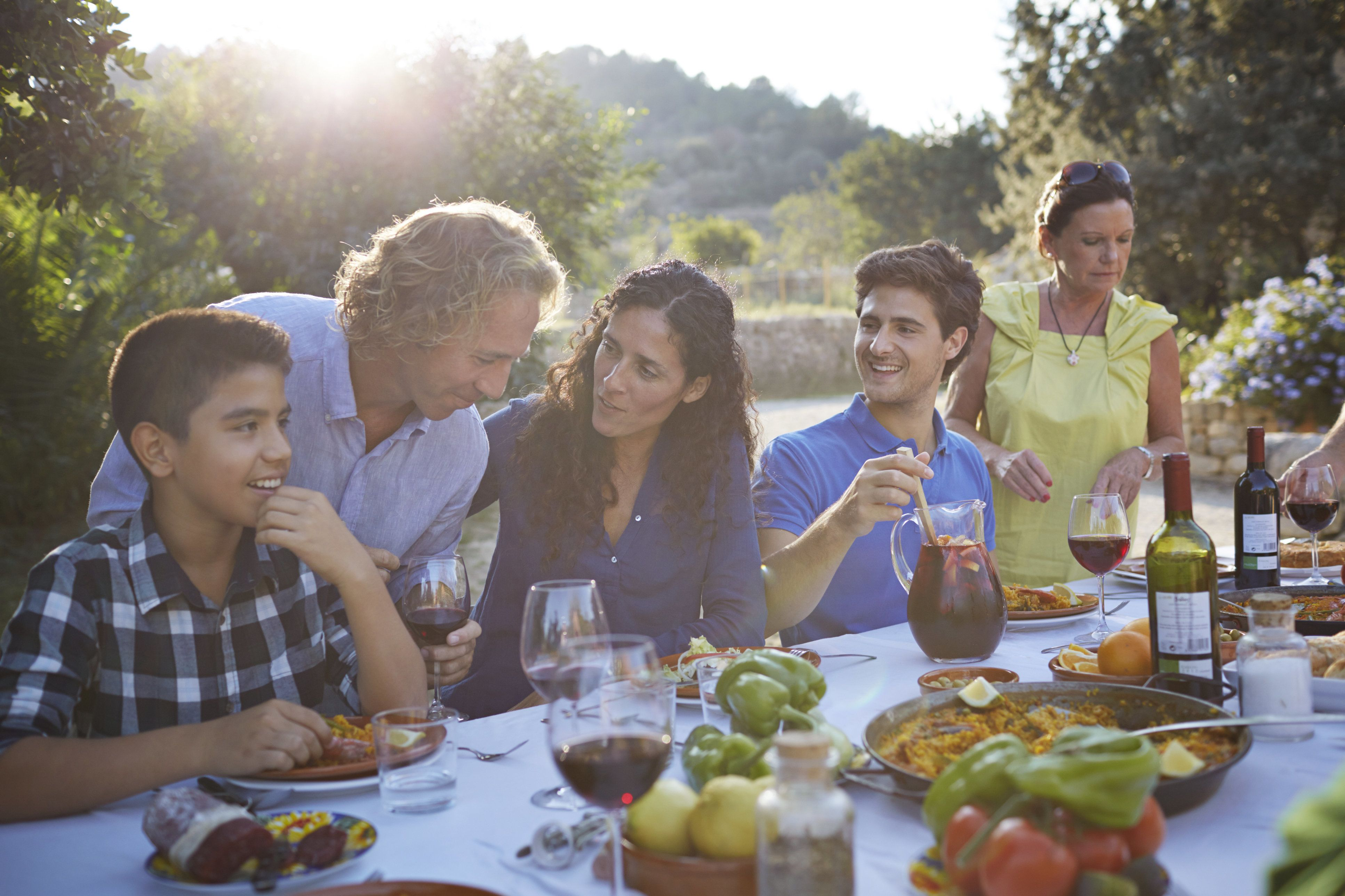 Multigenerational family laughing together at dinner table in garden at sunset