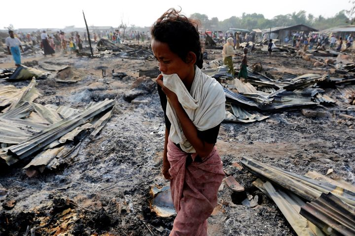 A woman walks among debris after fire destroyed shelters at a camp for internally displaced Rohingya Muslims in the western R