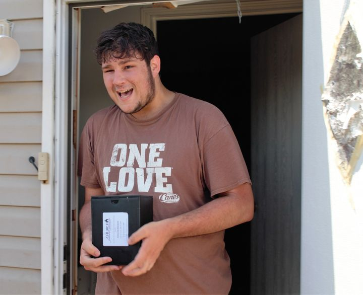 Cody Bourgeois, 20, emerges from his home in St. Amant, Louisiana, after the Cajun Navy helped him retrieve his mother's ashe