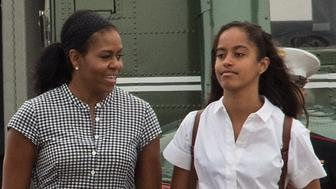 US President Barack Obama, First Lady Michelle Obama and daughters Malia and Sasha walk to board Air Force One at Cape Cod Air Force Station in Massachusetts on August 21, 2016 as they depart for Washington after a two-week holiday at nearby Martha's Vineyard. / AFP / NICHOLAS KAMM        (Photo credit should read NICHOLAS KAMM/AFP/Getty Images)