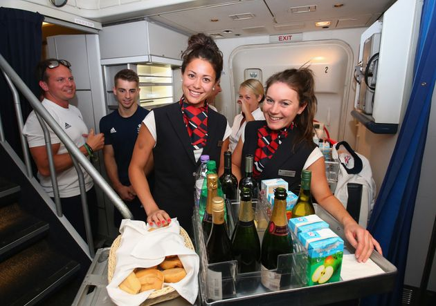 Sam Quek and Laura Unsworth of Great Britain dress up as cabin crew during the Team GB flight back from