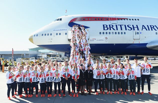 Team GB athletes pose for photos after landingat Heathrow