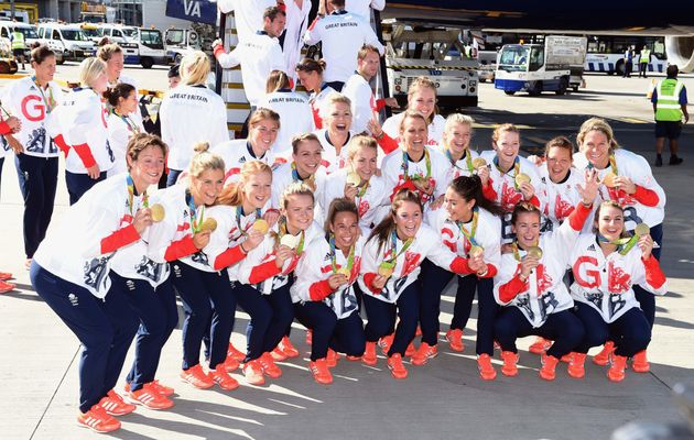Members of the women's gold medal winning hockey team pose for photos after arriving home at Heathrow